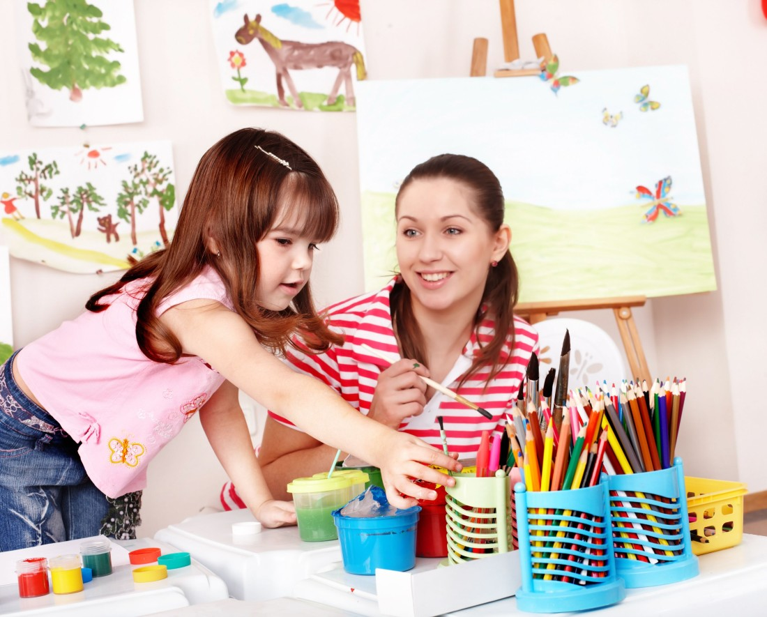 Child with teacher draw paints